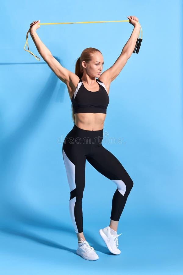 举胳膊的愉快和激动的白肤金发的女运动员,庆祝胜利 库存照片