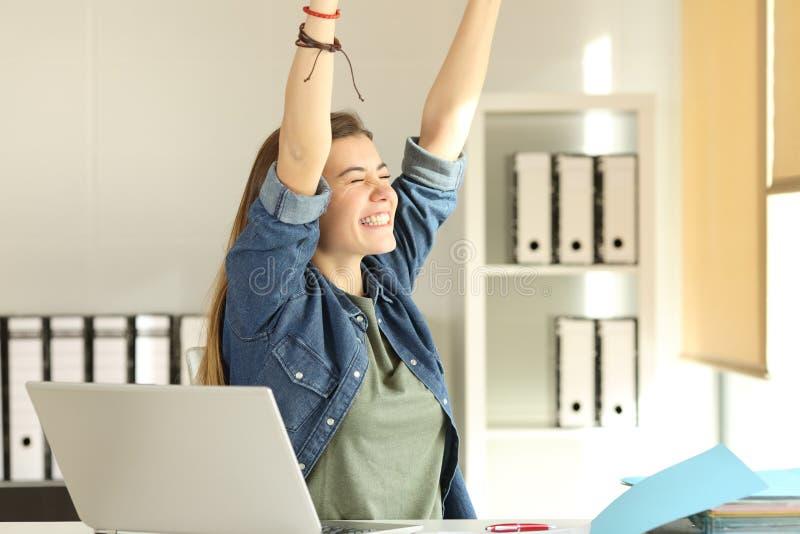 举胳膊的满意的实习生在办公室 库存图片