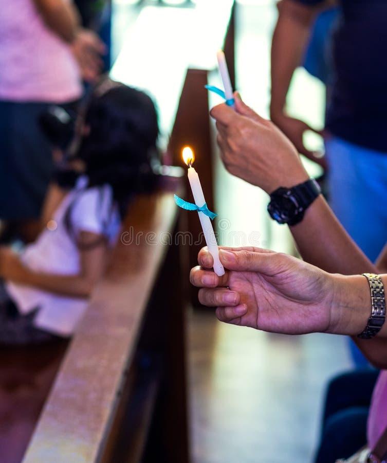 举蜡烛的手在洗礼仪式期间 免版税库存照片