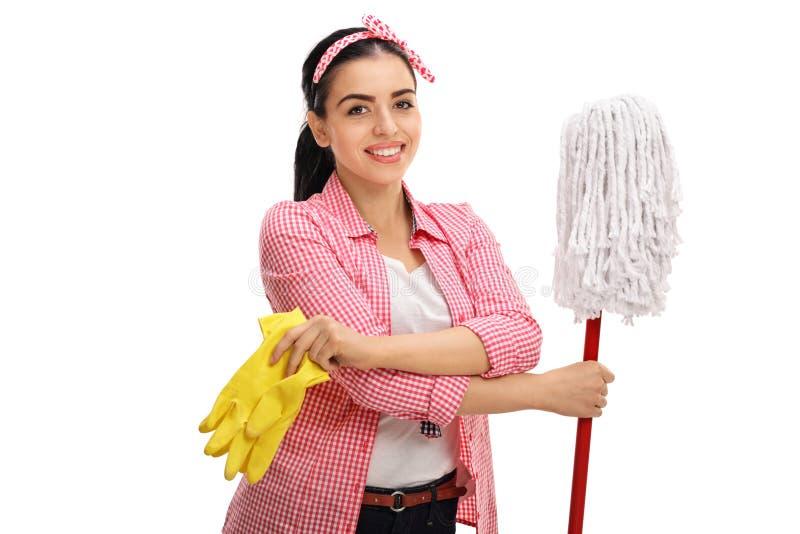 举行一个对清洁手套和拖把的快乐的少妇 免版税图库摄影