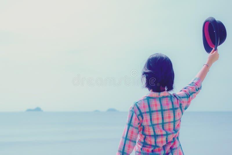 举行一个帽子和身分在海滩的女孩 免版税库存照片
