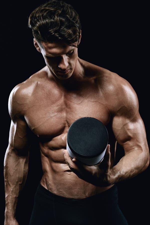 举行一个瓶子体育营养的美丽的运动人 免版税库存照片
