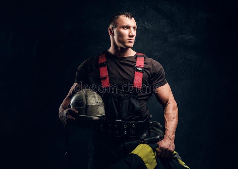 举行一个盔甲和夹克身分的残酷肌肉消防员在演播室对黑暗的织地不很细墙壁 免版税库存照片
