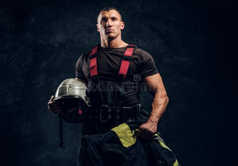 举行一个盔甲和夹克身分的残酷肌肉消防员在演播室对黑暗的织地不很细墙壁 图库摄影