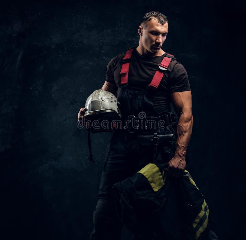 举行一个盔甲和夹克身分的残酷肌肉消防员在演播室对黑暗的织地不很细墙壁 免版税库存图片