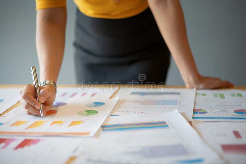 举行一张笔、理解饼和长条图在桌上的女商人手特写镜头在办公室 免版税库存图片