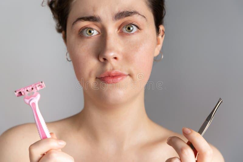 举行一把镊子和剃刀的一名年轻俏丽的妇女,不会取消在她的面孔的剩余头发 ??  免版税库存照片