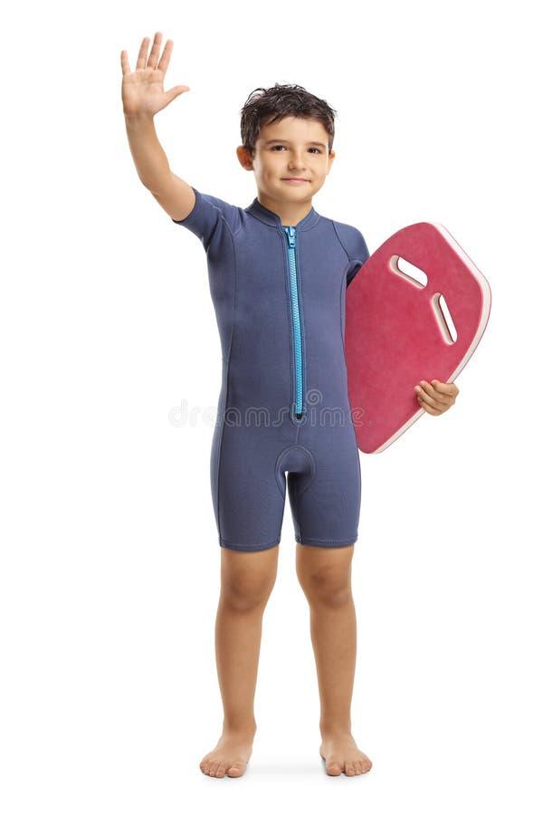 举行一游泳的浮游物板和挥动的保温潜水服的孩子 库存图片