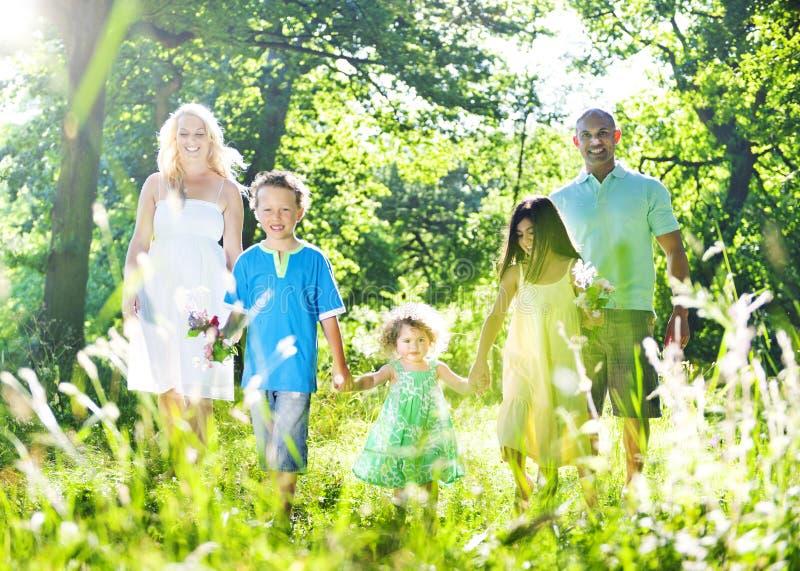 举行一起走通过森林概念的家庭 图库摄影