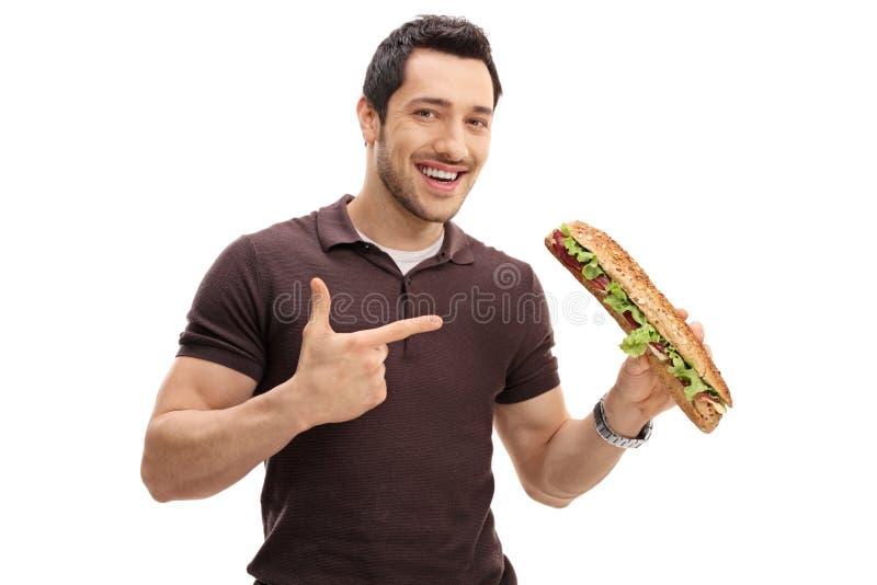举行三明治和指向的年轻人 免版税库存图片
