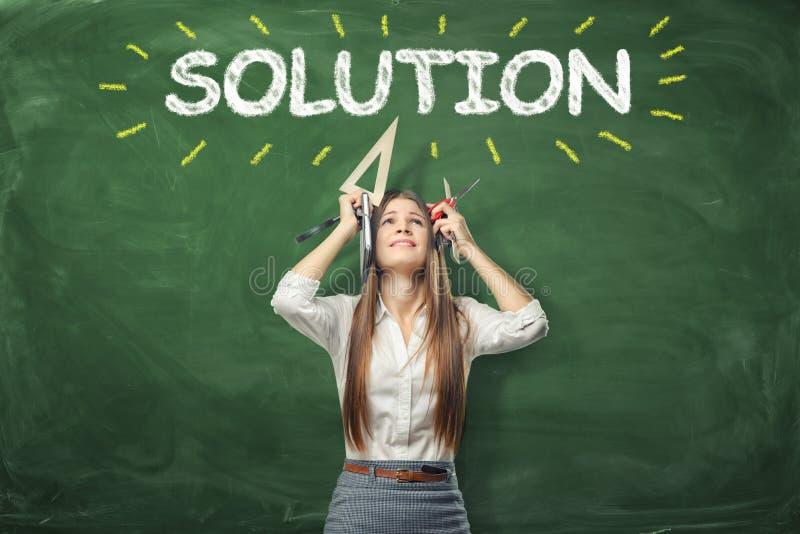 举行不同的办公用品和身分的少妇在手上在词'在她的头上'被写的解答下 免版税库存照片