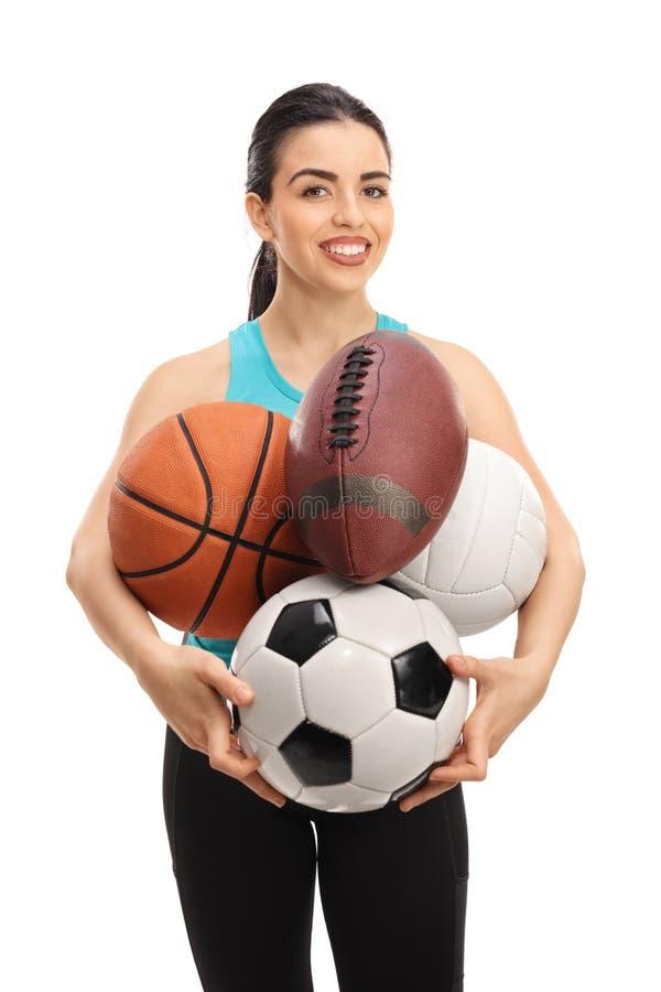 举行不同的种类体育球的少妇 免版税图库摄影
