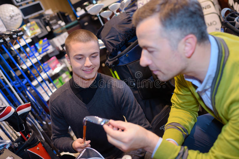 举行与手高尔夫俱乐部的人在高尔夫球商店 免版税库存照片