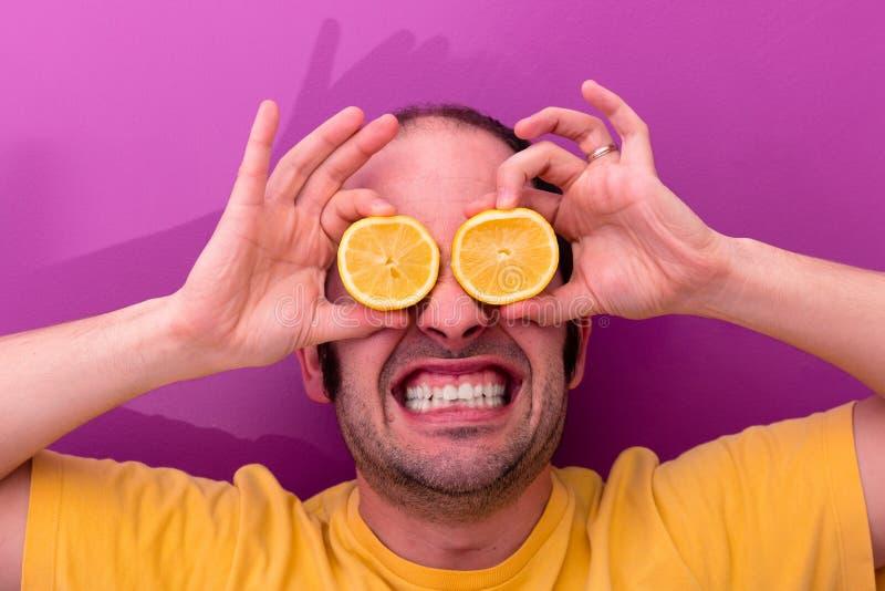 举行两的一个人的画象切了在他的眼睛的柠檬 免版税库存照片