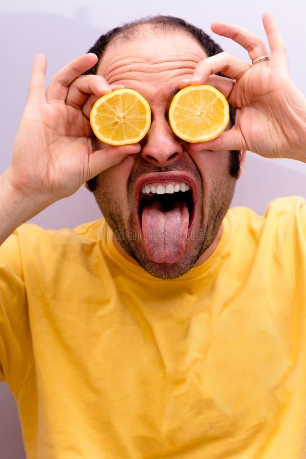举行两的一个人的画象切了在他的眼睛的柠檬 免版税库存图片