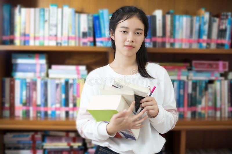 举行为选择的亚裔女学生在图书馆里预定 免版税图库摄影