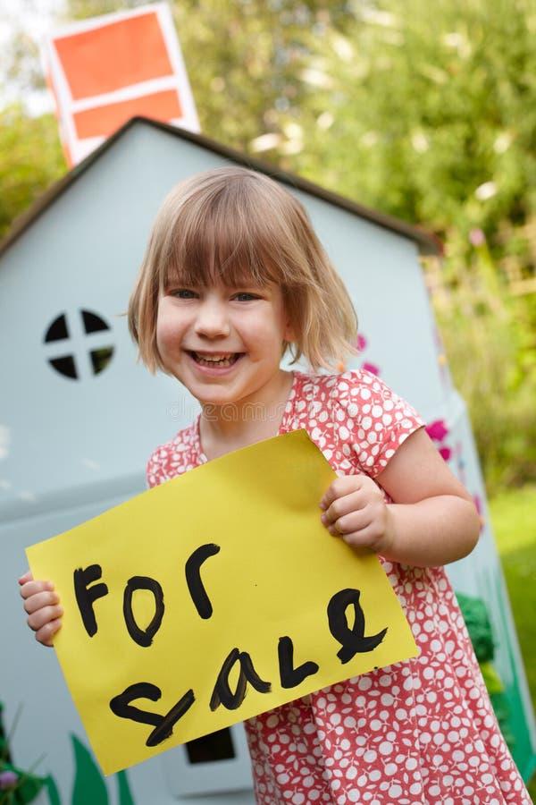 举行为销售标志的小女孩戏剧议院外 库存图片