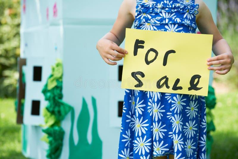 举行为销售标志的小女孩纸板剧场外 免版税图库摄影