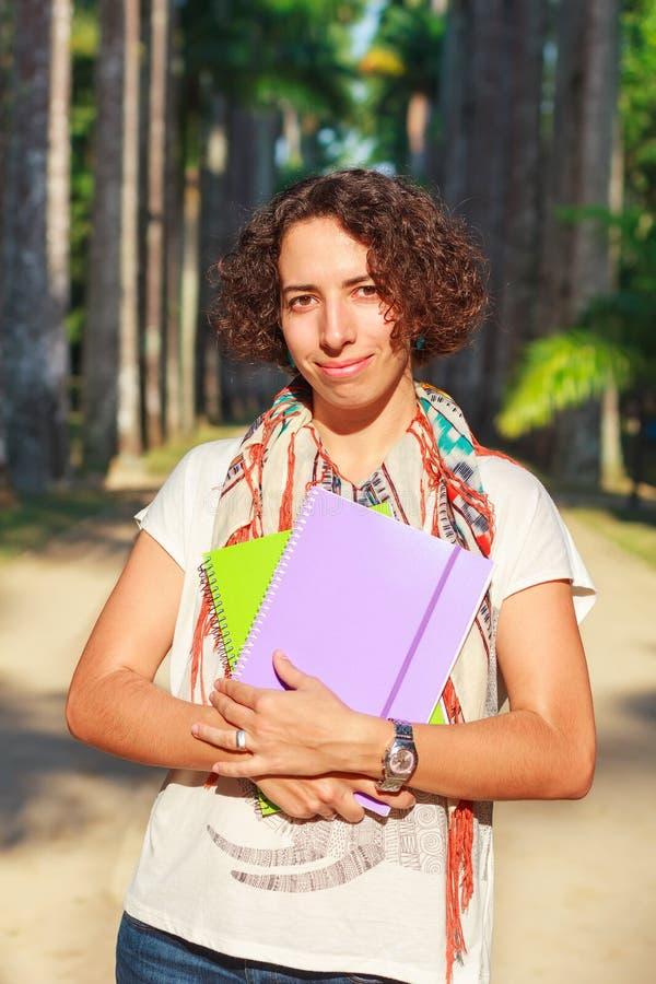 举行书和n的年轻愉快的微笑的妇女(学生,老师) 免版税库存照片