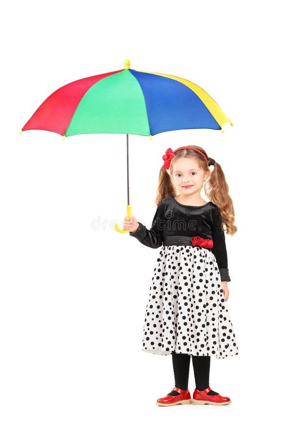举行五颜六色的一个逗人喜爱的小女孩的全长画象um 免版税图库摄影