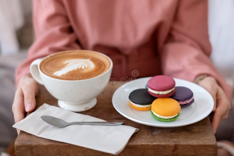 举行五颜六色的法国蛋白杏仁饼干和拿铁艺术的女性手 库存照片