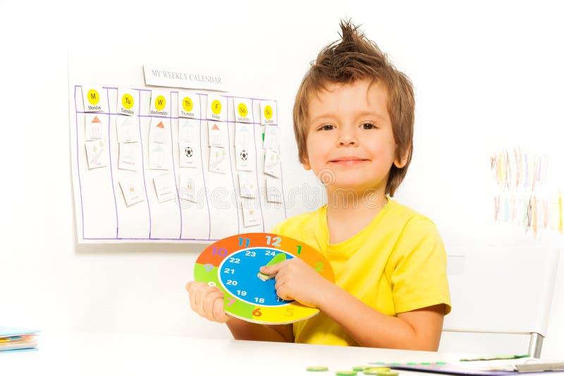 举行五颜六色的纸盒时钟开会的微笑的男孩 库存图片