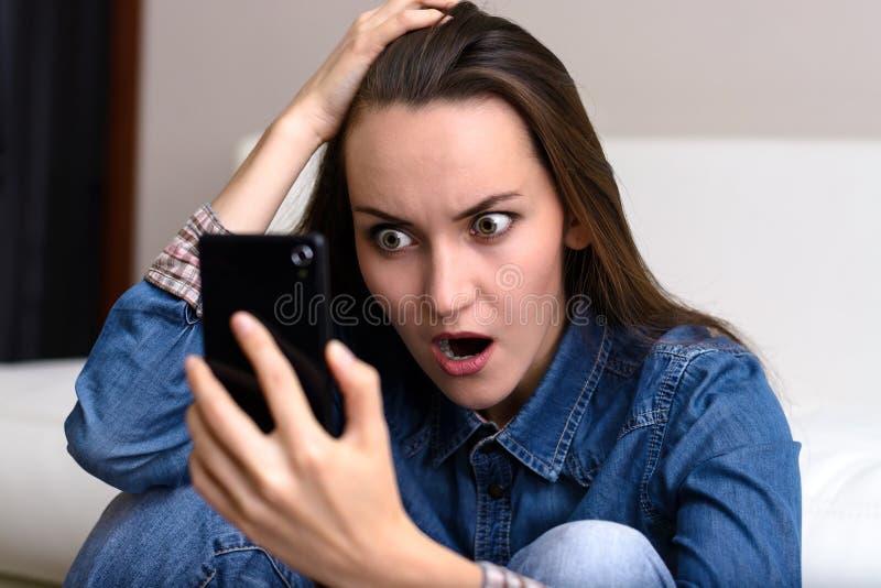 举行他的头和神色的少妇对智能手机 坐在震动的地板 免版税库存图片