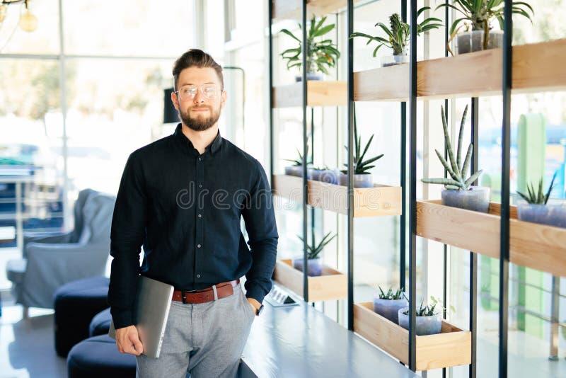 举行便携式计算机室内微笑的愉快的商人在办公室 免版税库存照片