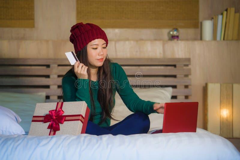 举行信用卡和圣诞礼物箱子购物的网上xmas的年轻美丽和愉快的亚裔韩国女孩提出微笑的satis 库存图片