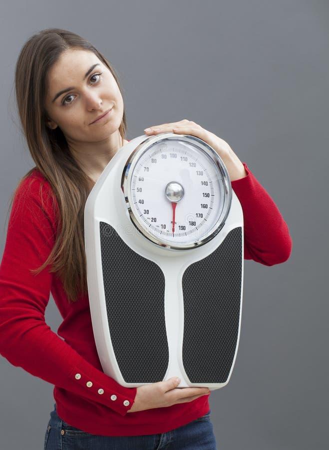 举行健身和重量控制标志的亭亭玉立的20s女孩 免版税图库摄影