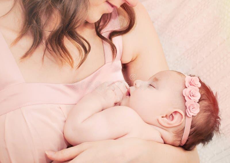 举行充满爱她小的逗人喜爱的睡觉婴孩美国兵的有同情心的母亲 库存照片