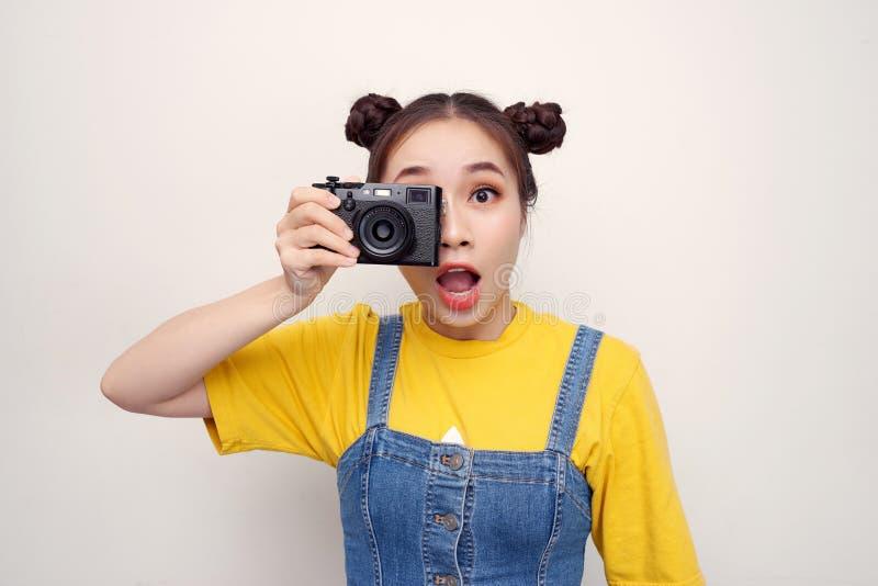 举行减速火箭的照相机在面孔和拍摄的激动的无固定职业的摄影师女孩的图象被隔绝在白色背景 图库摄影