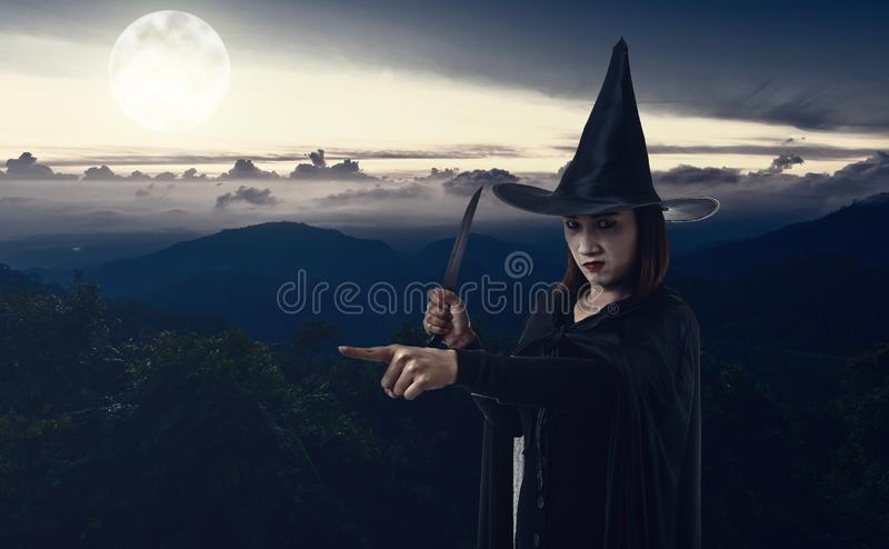 举行刀子机智的黑可怕巫婆万圣夜服装的妇女 免版税图库摄影