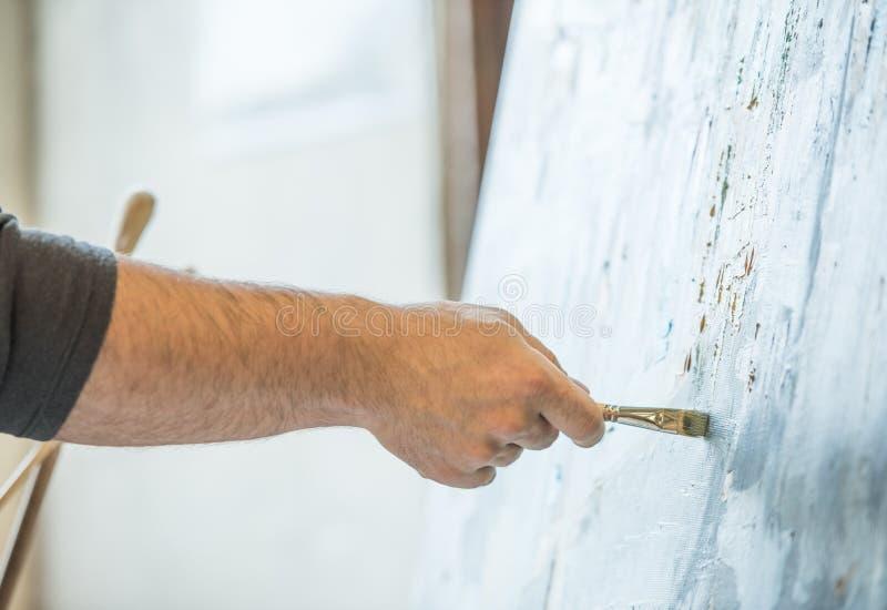 举行刷子和绘的一个人的手 库存图片
