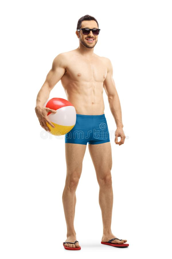 举行可膨胀的游泳的短裤的英俊的适合的人 免版税库存图片