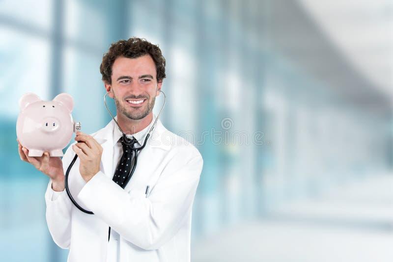 举行听有听诊器的存钱罐的Miling医生 库存图片