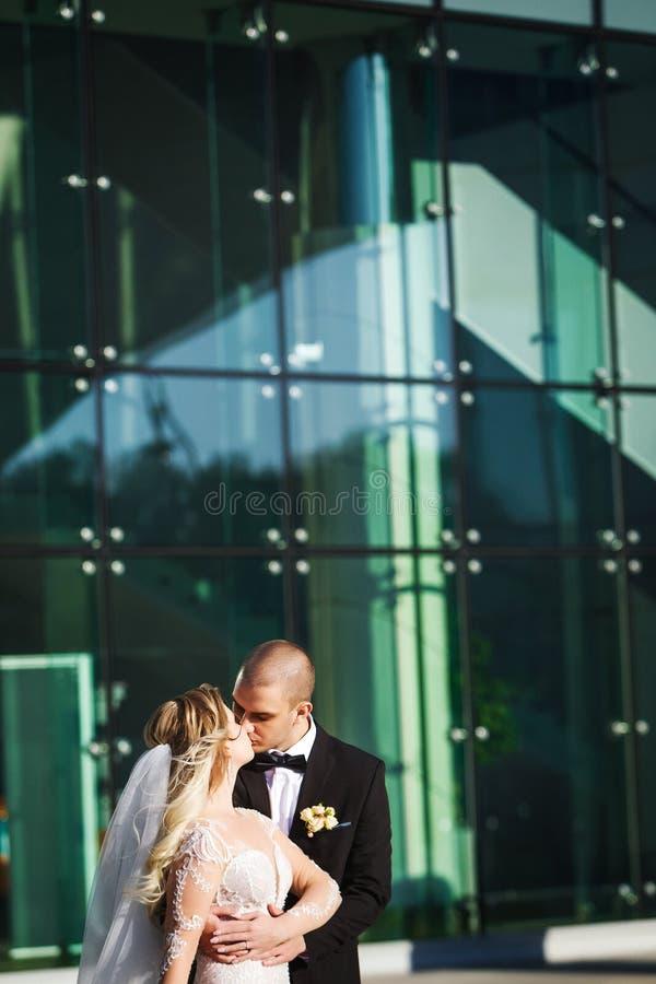 举行和亲吻在未来派大厦附近的新娘和新郎 免版税库存照片