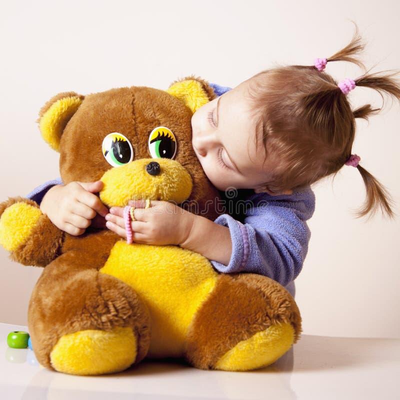 举行和亲吻玩具熊童年, jo的逗人喜爱的女婴 免版税图库摄影
