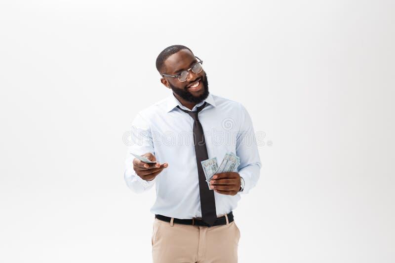 举行和指向金钱的年轻快乐的黑商人隔绝在白色 免版税库存图片