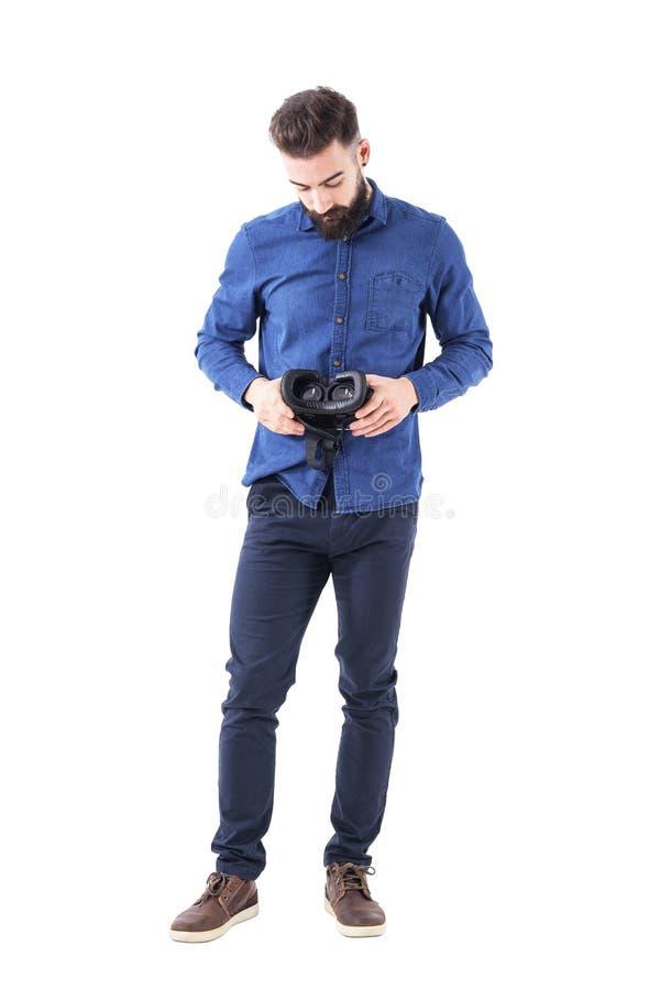 举行和看在审查的vr耳机下的年轻有胡子的商人正面图  图库摄影