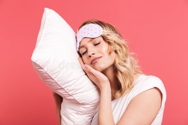 举行和说谎在白色枕头的梦想的年轻女人20s佩带的睡觉面具画象  库存照片