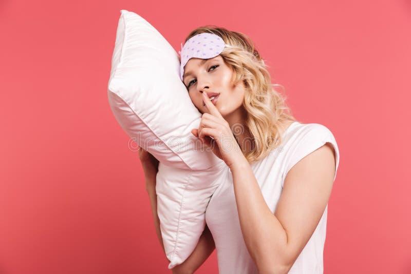举行和说谎在白色枕头的满意的年轻女人20s佩带的睡觉面具画象  库存图片