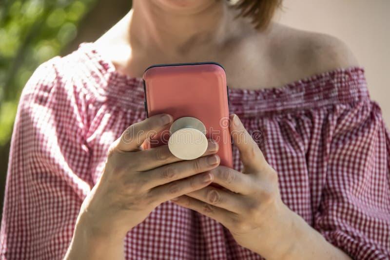 举行和读从在桃红色案件的一个手机的妇女特写镜头与夹子把柄在后退肩膀女衬衫和短小 免版税库存图片