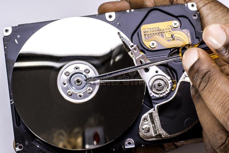 举行和运转在多灰尘的与scewdriver的计算机硬盘的男性技术员手 库存照片