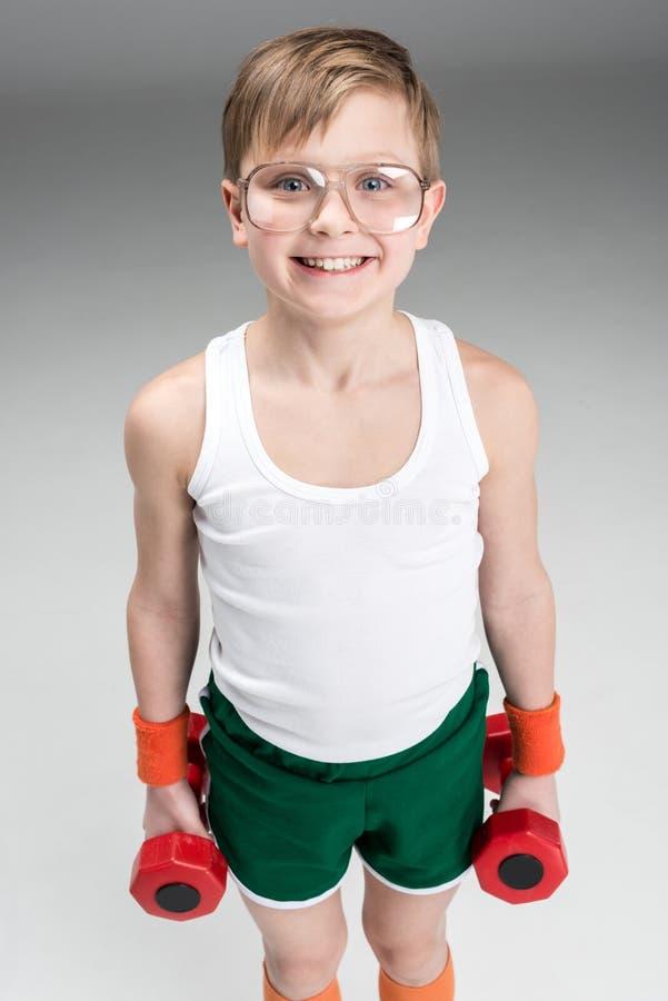 举行哑铃的微笑的男孩画象 免版税库存图片