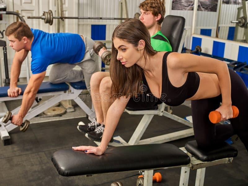 举行哑铃锻炼的妇女在健身房 免版税库存图片