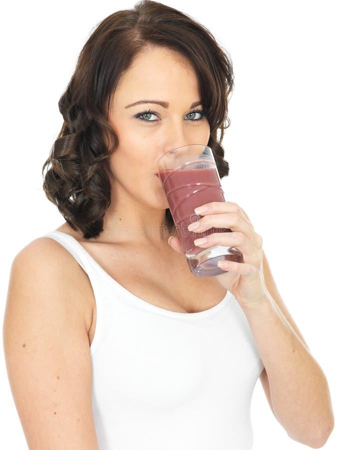 举行喝的年轻健康愉快的妇女一杯新鲜的混杂的莓果圆滑的人 免版税库存图片