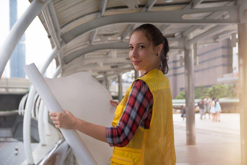 举行图纸计划的年轻女性建筑师 免版税库存图片