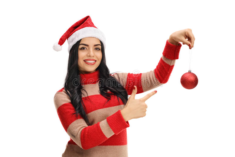 举行圣诞节装饰品和指向的愉快的少妇 库存照片