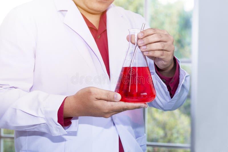 举行在一件白色外套的成熟科学家的画象人在实验室 免版税图库摄影